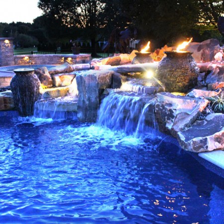 poolside patio with waterfall night time view