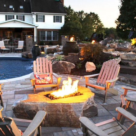 poolside patio with fire boulder lit