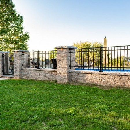 gate surrounding poolside patio with waterfall