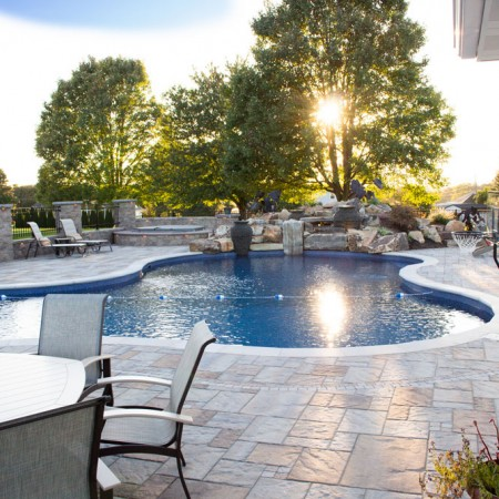 sun setting with poolside patio with waterfall